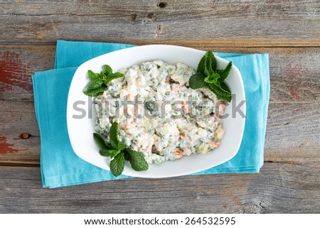 Simple Olivier Salad on old picnic table garnished with mint - stock photo