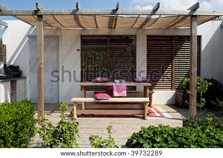 simple outside living place with wood elements and red touch - stock photo