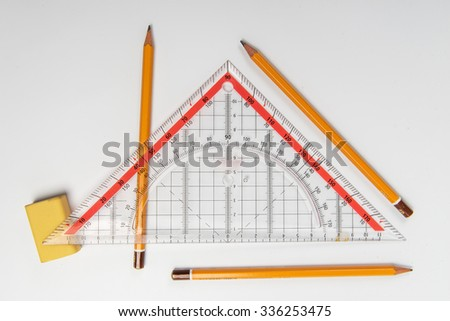 Simple pencils, eraser and ruler a triangle on a light background - stock photo