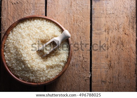 Simple rice in a wooden bowl on a wooden background, top view