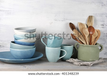 Simple rustic blue crockery against white wooden wall: dish, stack of bowls. mugs and wooden cooking utensil set in rough ceramic pot.