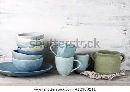 Simple rustic handmade crockery against wooden wall: dish, stack of bowls, mugs and rough ceramic pot.