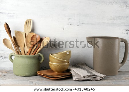 Simple rustic kitchenware against white wooden wall: rough ceramic pot with wooden cooking utensil set, stacks of ceramic bowls, jug and wooden trays. - stock photo