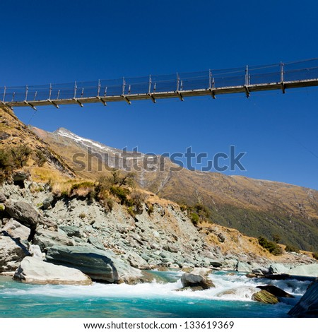 Simple suspension swing bridge crossing high over a rocky glacial mountain river in Mount Aspiring National Park  South Island  New Zealand - stock photo