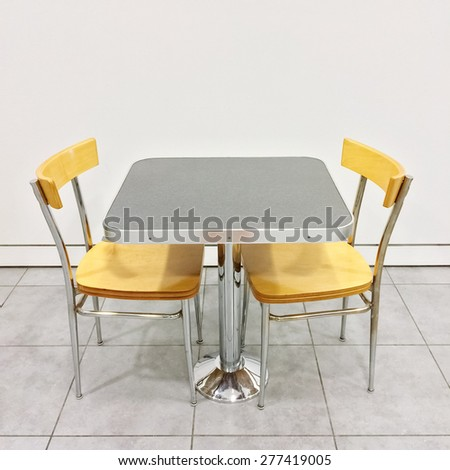 Simple table with two chairs in a cafeteria. - stock photo