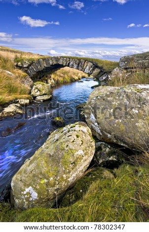 simple traditional single layer arched stone bridge for sheep across a small stream in wales - stock photo