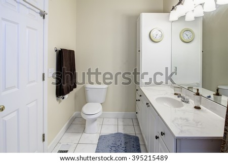 Simple white bathroom with tile and marble sink - stock photo