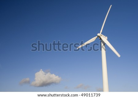 simple wind turbine isolated over a blue sky with one cloud. Alternative energy source - stock photo