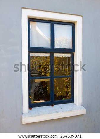 Simple window in a smooth plastered wall with a reflection of autumn leaves