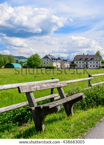 Simple wooden bench on the edge of a gorgeous green Alpine meadows, behind which a wooden fence and a traditional Austrian farmhouse on the background of snowy mountains and blue sky with clouds