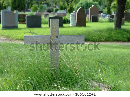 Simple wooden cross in an outdoor cemetery. - stock photo