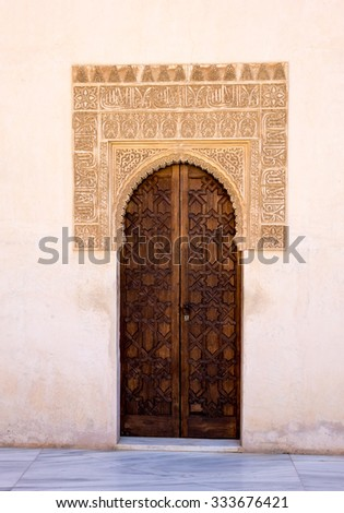 Simple wooden doorway with ornate arch in courtyard of Alhambra palace Granada, Spain - stock photo