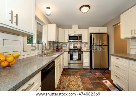 Simple yet practical kitchen interior with white modern cabinets, grey granite counter top and stone tile flooring. Northwest, USA