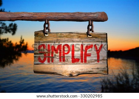Simplify motivational phrase sign on old wood with blurred background - stock photo