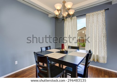 Simplistic dinning room with gray walls, and black table chair set. - stock photo