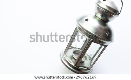 Simplistic tealight candle holder or lantern lamp made of glass and galvanised metal with starry design. Isolated on white background. Slightly de-focused and close-up shot. Copy space.