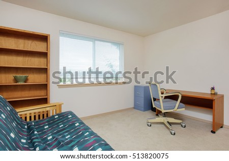 Simply furnished home office interior. There is a wooden sofa in green color, empty bookcase standing nearby and desk with a chair. Northwest, USA