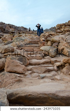 SINAI MOUNTAINS, EGYPT - NOVEMBER 28, 2013: Unidentified people descend along the stairs from the cobblestones from the top of Mount Moses, Egypt - stock photo