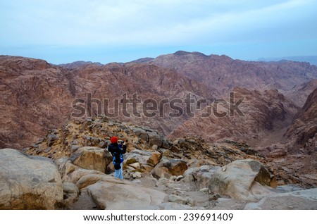 SINAI MOUNTAINS, EGYPT - NOVEMBER 28, 2013: Unknown girl photographs the morning view from the top of Mount Moses - stock photo