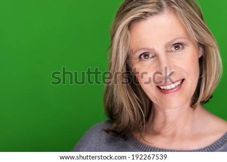Sincere concerned attractive middle-aged woman with shoulder length blond hair looking directly at the camera with a smile, on green with copyspace - stock photo