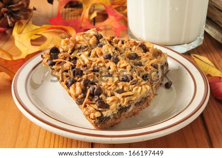 Sinfully delicious dessert bars with chocolate chips, coconut, and a glass of milk - stock photo