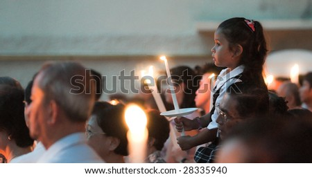 SINGAPORE - APR 10: An unidentified girl sits on her father's shoulder holding a lighted candle at a Good Friday Mass conducted at St. Joseph's Church April 10, 2009 in Singapore. - stock photo