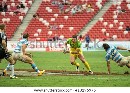 SINGAPORE-APRIL 16: Australia 7s Team (yellow/green) plays against Argentina 7s team (blue/white) during Day 1 of HSBC World Rugby Singapore Sevens on April 16, 2016 at National Stadium in Singapore