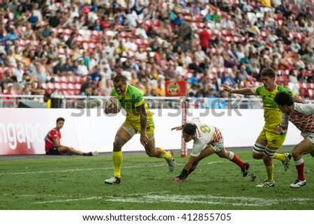 SINGAPORE-APRIL 16: Australia 7s Team (yellow/green) plays against Japan 7s team (red/white) during Day 1 of HSBC World Rugby Singapore Sevens on April 16, 2016 at National Stadium in Singapore - stock photo