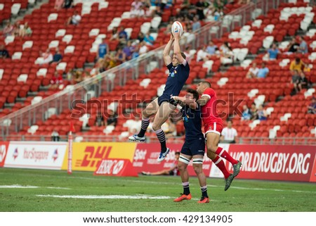 SINGAPORE-APRIL 17:Canada 7s Team (red) plays against Scotland 7s team (navy blue) during Day 2 of HSBC World Rugby Singapore Sevens on April 17, 2016 at National Stadium in Singapore