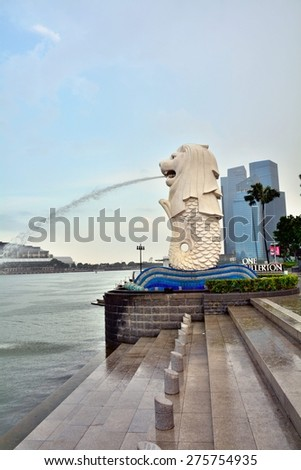 SINGAPORE - APRIL 30,2015: Financial district skyscrapers and Merlion at Marina bay. The Merlion is a traditional creature with a lion head and a body of a fish, seen as a symbol of Singapore. - stock photo