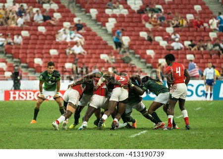 SINGAPORE-APRIL 16: Kenya 7s Team (red) plays against South Africa 7s team (green) during Day 1 of HSBC World Rugby Singapore Sevens on April 16, 2016 at National Stadium in Singapore