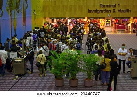 SINGAPORE APRIL 29: Passengers wait in line at Singapore International Airport on April 29, 2009 in Singapore. Staff members wear face masks because of the outbreak of Swine flu. - stock photo