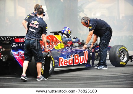 SINGAPORE - APRIL 24: Red Bull Racing pit crews cooling the F1 RB6 car after David Coulthard performed donuts during Red Bull Speed Street Singapore on April 24, 2011 in Singapore. - stock photo