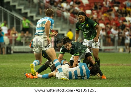 SINGAPORE-APRIL 17:South Africa 7s Team plays against Argentina 7s Team (blue/white) during Day 2 of HSBC World Rugby Singapore Sevens on April 17, 2016 at National Stadium in Singapore