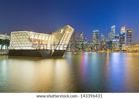SINGAPORE - April 5: The futuristic building housing Louis Vuitton store mirrors on the quiet waters of Singapore bay circa Apri 5,l 2013 in Singapore. - stock photo