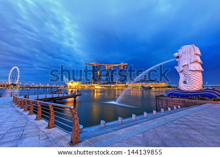 SINGAPORE - APRIL 06: The Merlion fountain in front of the Marina Bay Sands hotel on April 06, 2013 in Singapore. Merlion is a imaginary creature with the head of a lion, seen as a symbol of Singapore - stock photo