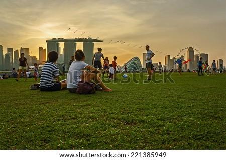 SINGAPORE - April 12 : Tourists watching the sunset at Marina Barrage Singapore on April 12, 2014 - stock photo