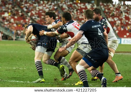 SINGAPORE-APRIL 17:USA 7s Team (white) plays against Scotland 7s team (navy blue) during Day 2 of HSBC World Rugby Singapore Sevens on April 17, 2016 at National Stadium in Singapore