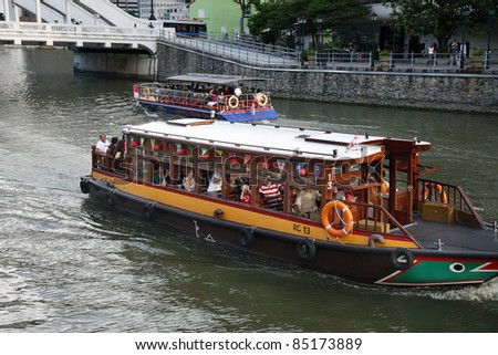 SINGAPORE - AUGUST 21: A tourist boat moves along the river on August 21, 2010 in Singapore. The Singapore River Cruise is one of the main tourist attractions in this former British colony. - stock photo