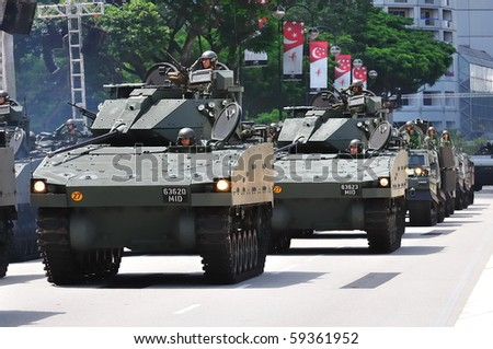 SINGAPORE - AUGUST 09: Columns of Bionix armored fighting vehicles parading during Singapore National Day Parade 2010 at the Padang August 09, 2010 in Singapore - stock photo