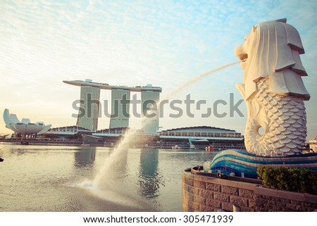 SINGAPORE - AUGUST 2: The Merlion fountain in front of the Marina Bay Sands hotel on August 2, 2015 in Singapore. Merlion is a imaginary creature with the head of a lion, seen as a symbol of Singapore - stock photo
