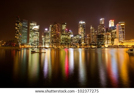 Singapore business district in the night time with water reflections. - stock photo