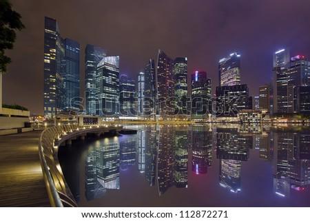 Singapore Central Business District City Skyline Along Marina Bay Boardwalk at Night - stock photo