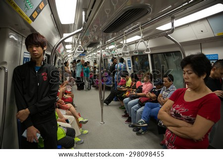 SINGAPORE - CIRCA FEBRUARY, 2015: Passengers in the train MRT. Singapore subway, also known as MRT, started operating in 1987. It is network length is 130 kms, it has 87 stations and 4 lines. - stock photo