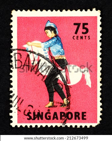 SINGAPORE - CIRCA 1968: Red color postage stamp printed in Singapore with image of a traditional Kuda Kepang dancer on a horse prop.m - stock photo