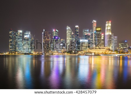 Singapore city at night. And building a new skyscraper in downtown at night.