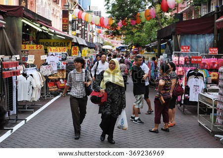 SINGAPORE CITY, SINGAPORE - NOV 13, 2013: Shoppers walk along a busy street  in the city state's Chinatown market district. The area is popular with locals and tourists for its stores and restaurants. - stock photo