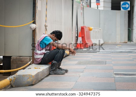 SINGAPORE - 21 DEC 2013: Exhausted construction worker sits on a cement slab at a project worksite in Singapore to take a break. - stock photo