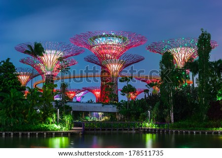 SINGAPORE -DEC 31: Futuristic view of amazing illumination at Garden by the Bay on Dec 31, 2013 in Singapore. Night light show at Supertree Groveis is main Marina Bay Sands district tourist attraction - stock photo