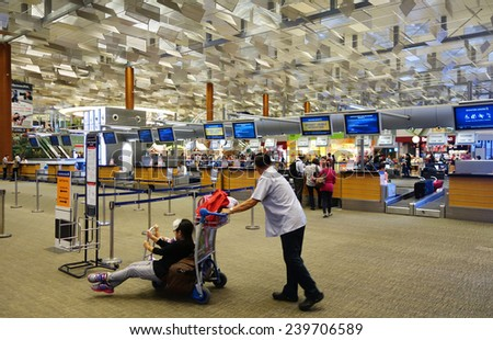 SINGAPORE - DEC 03: Passengers check in Changi International Airport on December 03, 2014 in Singapore. Changi Airport serves more than 100 airlines connecting Singapore to over 220 cities - stock photo